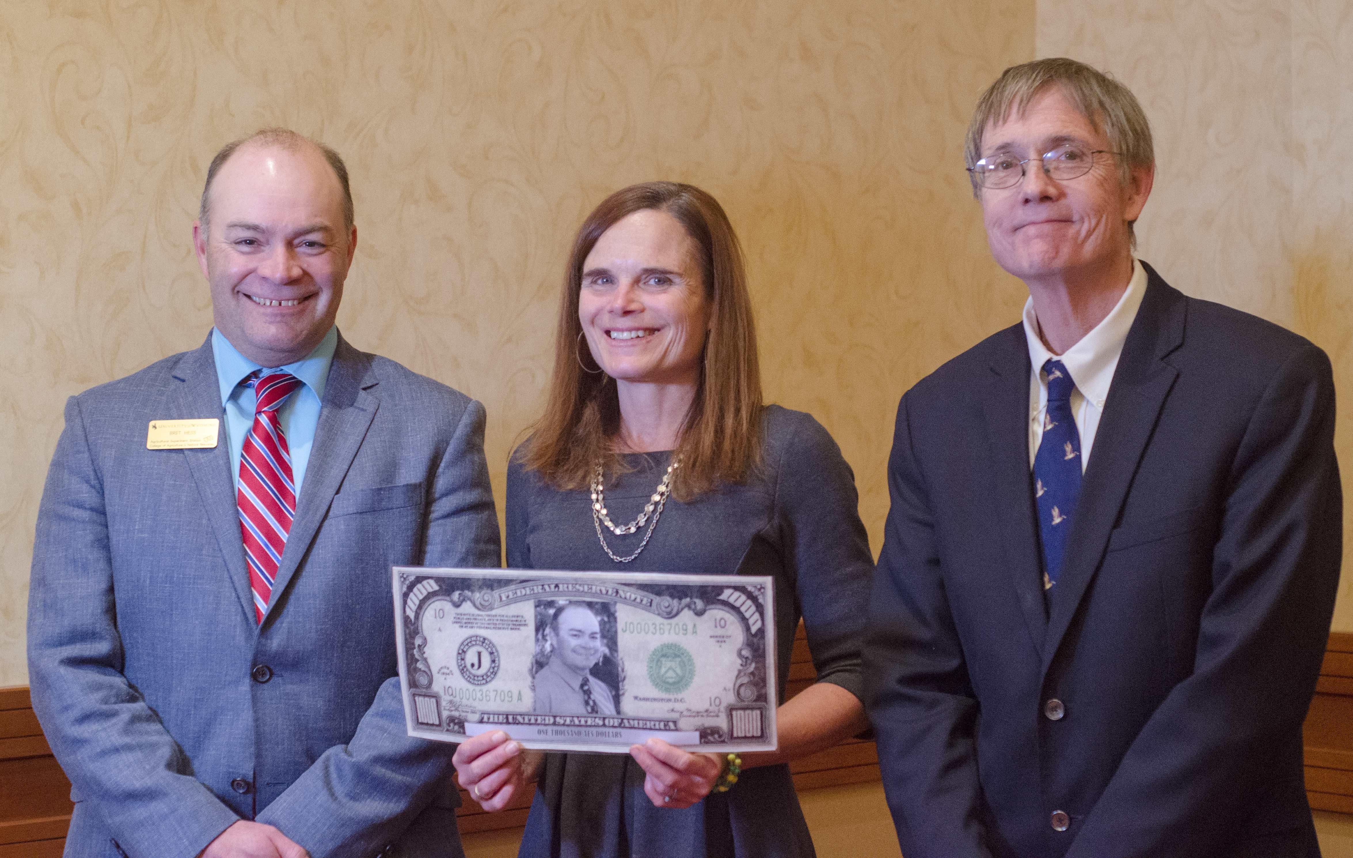 Larson-Meyer holding large fake money.