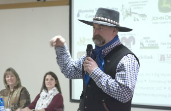 Man in black cowboy hat and vest giving presentation.