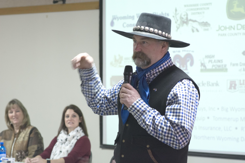 Man in black cowboy hat and vest giving presentation.