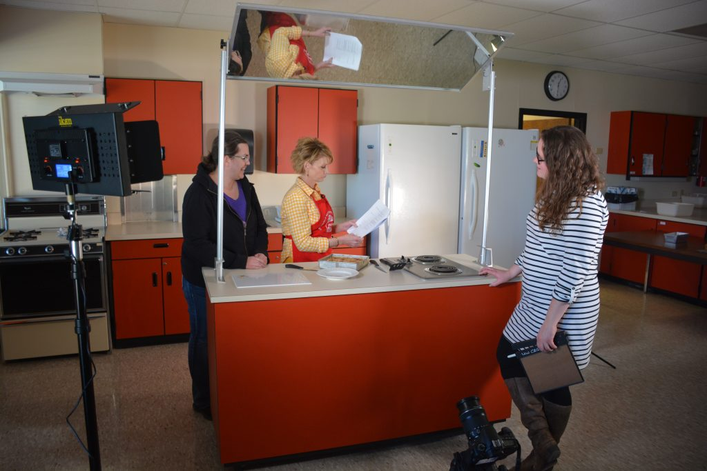 Three women stand around the rolling island counter used as the set for the video series.