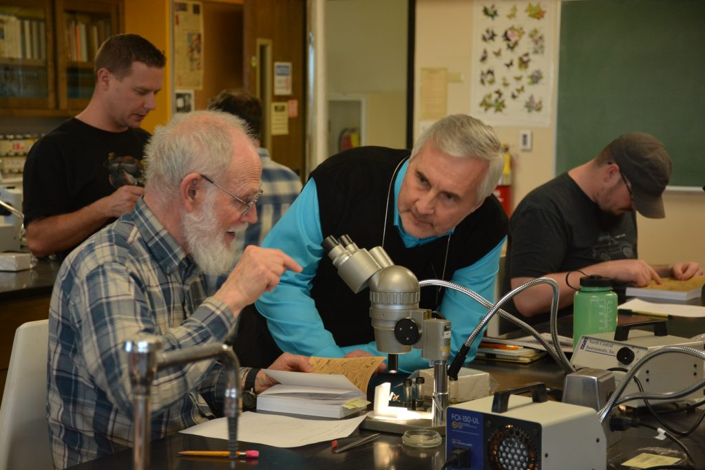 Man with gray beard gestures toward microscope as other man leans closely to listen.