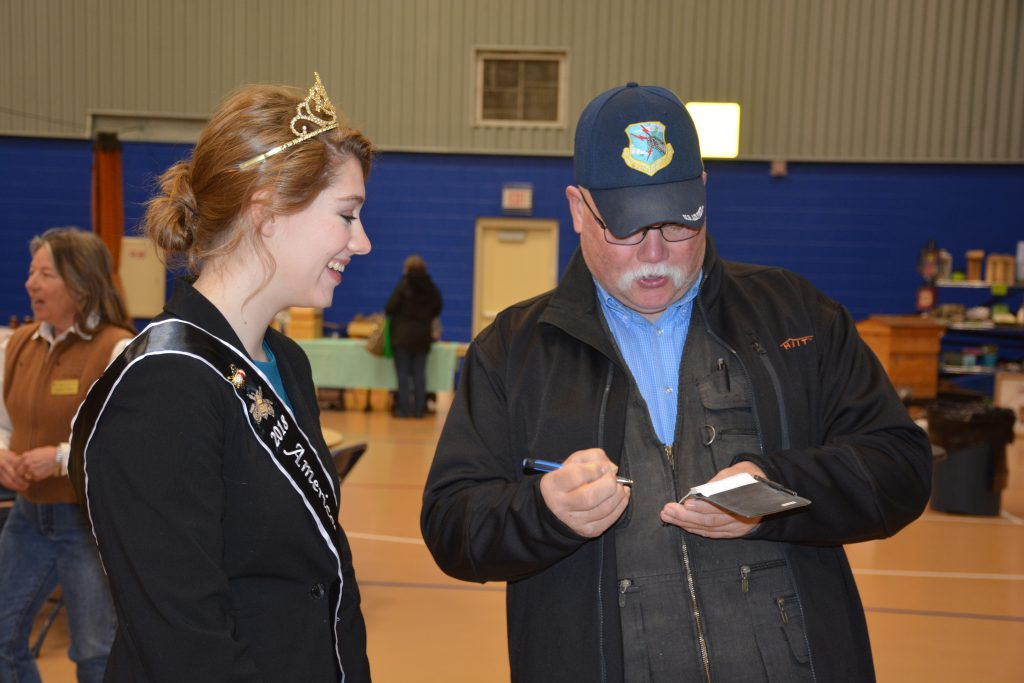 Man in cap with notebook talks to smiling woman wearing a tiara.