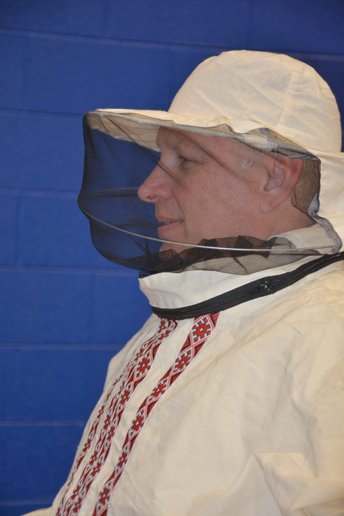 Man in embroidered canvas beekeeper jacket and veil.