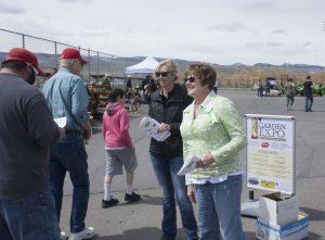 Women greet guests entering fair grounds.