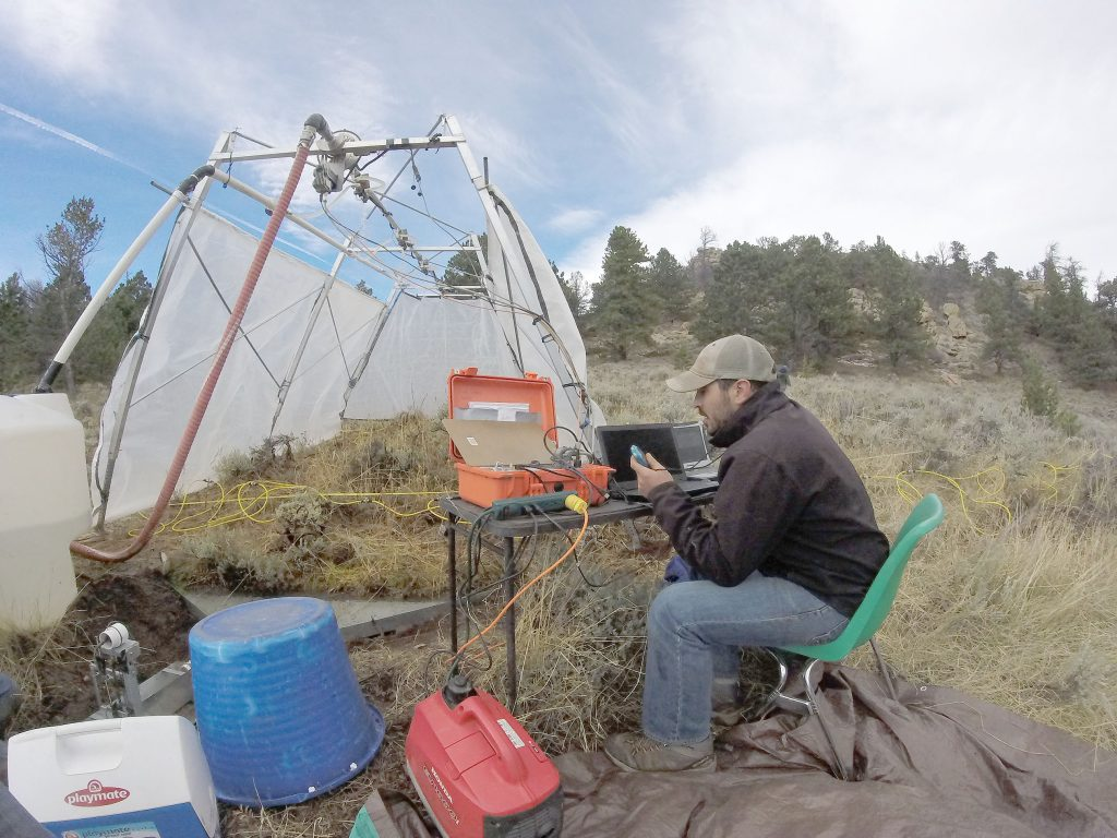 Researcher seated at camp table timing water flows with various pieces of equipment.