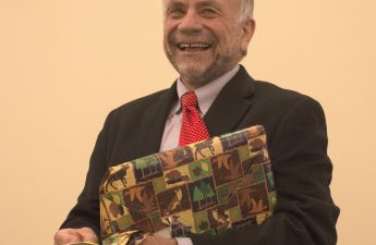 Glen smiling and holding a wrapped present